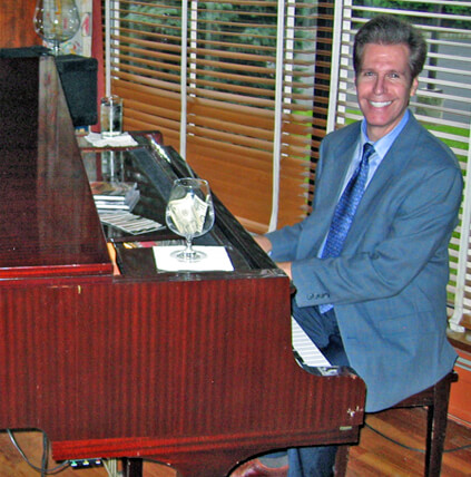 Arnie playing the piano at a cocktail hour.